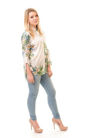 jeans apretados: Retrato de una hermosa chica adolescente rubia vistiendo pantalones azules, una camisa blanca de flores y zapatos de tacón de color rosa aisladas sobre un fondo blanco