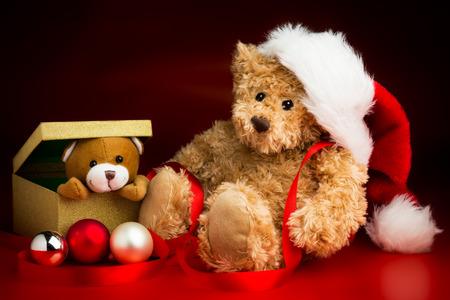 Un oso de peluche marrón que llevaba un sombrero de Navidad que se sienta al lado de una caja con un oso de peluche que mira a escondidas sobre el borde aislado contra un fondo rojo y negro Foto de archivo