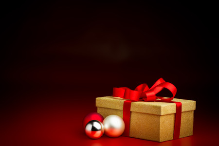 closed ribbon: Closed golden present box with a red ribbon three baubles isolated against a black and red background