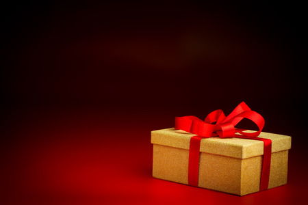 closed ribbon: A closed golden surprise present box with a red ribbon isolated against a black and red background
