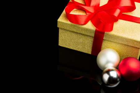 closed ribbon: Closed golden present box with a red ribbon three baubles isolated against a black background