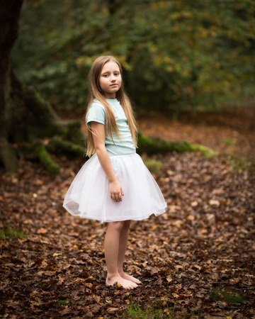 bare feet girl: Portrait of a shy young child girl with long dark blond hair wearing a tutu skirt and bare legs and feet standing alone in a dark autumn forest clearing. Stock Photo