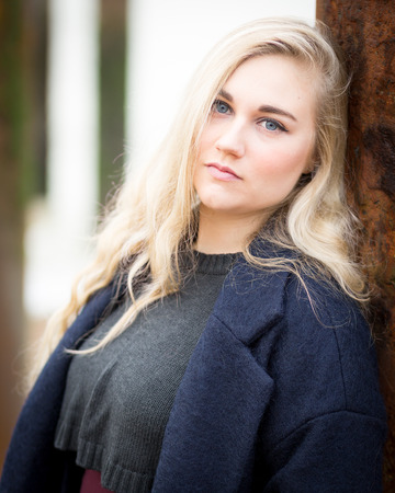 woolly: Portrait of a beautiful blond young teenage girl with long wavy hair woolly jumper and warm long coat standing alone on a cold beach in the wind.