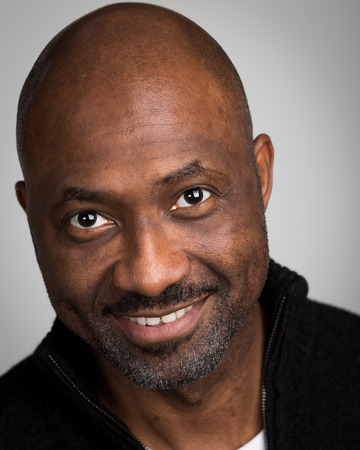 Portrait of a bald unshaven black man with a mustache wearing a black cardigan isolated against a grey background