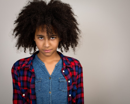 wacky: Portrait of a beautiful mixed race girl with wacky afro hair style  in a checkered shirt isolated against a grey background.