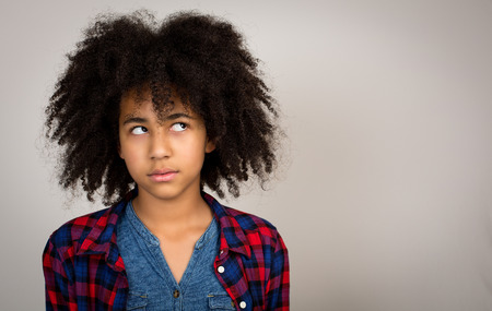 wacky: Young teenage girl with wacky afro hair looking up thinking and solving problems isolated against a grey background. Stock Photo