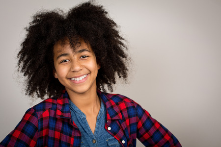 wacky: Portrait of a beautiful mixed race girl with wacky afro hair style laughing in a checkered shirt isolated against a grey background.