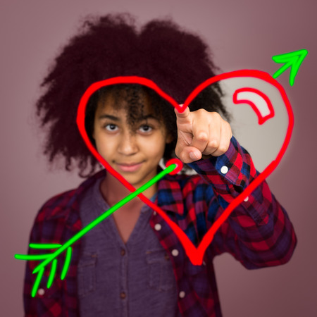 race relations: A mixed race teenage girl with afro hairstyle drawing a love heart with arrow in the air.