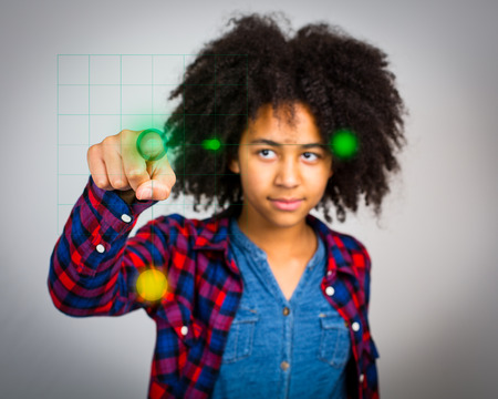 wacky: A mixed race teenage girl with wacky afro hair playing a virtual game in the air in front of her isolated against a grey background.