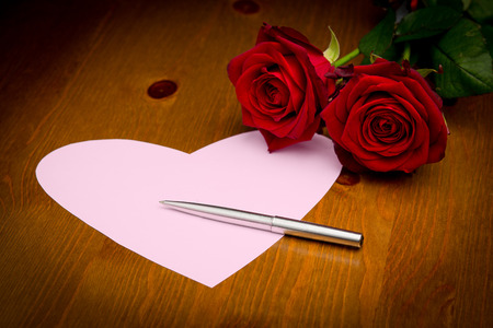 Pink note paper in the shape of a love heart on a wooden surface with two roses a pen and copy space. photo