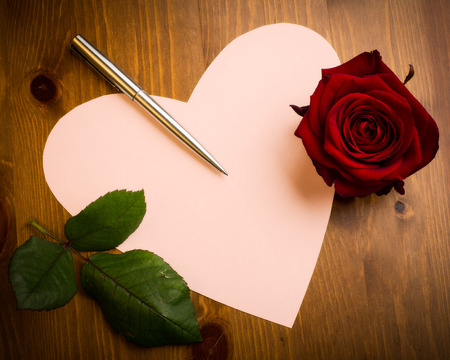 A Valentine love heart note paper on a wooden surface with pen, a single rose and copy space. photo