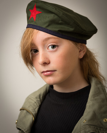 Studio portrait of a teenage ginger girl with long hair wearing a Che revolution barret hat and a green army jacket isolated against a grey background. photo