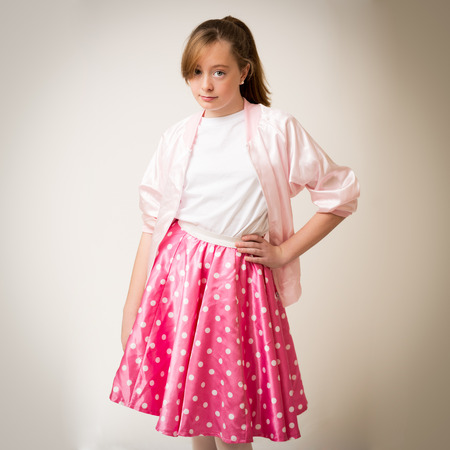 petticoat: Portrait of a teenage ginger girl with long hair in a pony tail wearing a pink sixties rock and roll jacket and skirt.