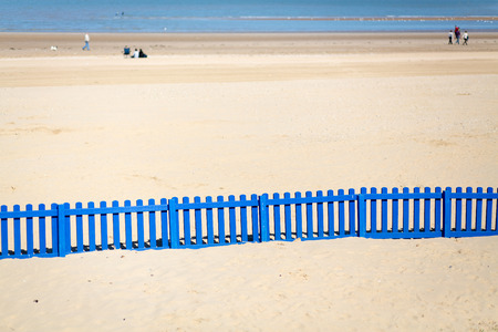 cutting through: A long low blue wooden fence cutting through white sand on the beach. People out of focus in the distance enjoying the sun.