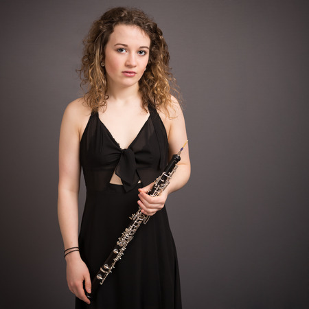 oboe: Portrait of a beautiful young female oboe player in a black dress with long curly hair standing in front of a dark grey background.
