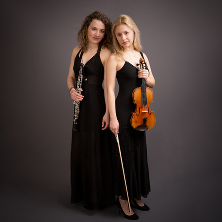 duo tone: Portrait of two beautiful young female classical music artists, a oboist and a violinist. Both in a long black dress and high heels isolated against a dark grey background.