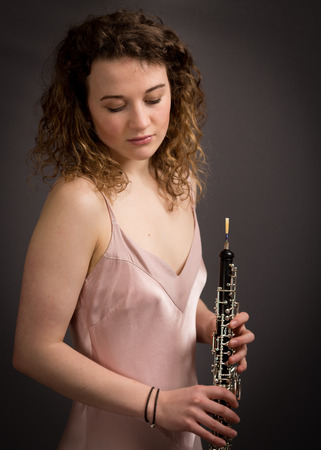 oboe: Studio portrait of a beautiful young woman with curly hair in a pink dress holding an oboe looking down isolated against a dark grey background.
