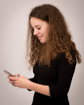 Beautiful teenage girl with long curly ginger hair sending text messages on her phone. photo