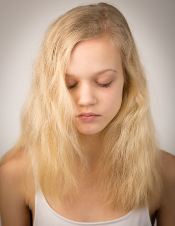 Portrait of a blond teenage girl with her eyes closed and wearing a white top. Stock Photo