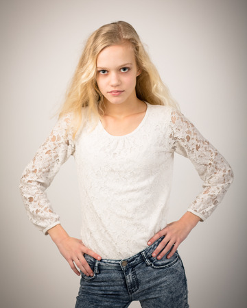 isolated on grey: Studio portrait of a beautiful teenage blond girl with long hair wearing jeans and a white lace top. Stock Photo