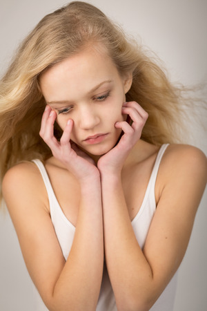 wind down: Studio shot of a beautiful teenage girl with long hair blowing in the wind with her hands on her face looking down.
