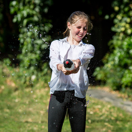 Wet teenage girl in white shirt and black legging squeezes water from plastic bottle. Stock Photo