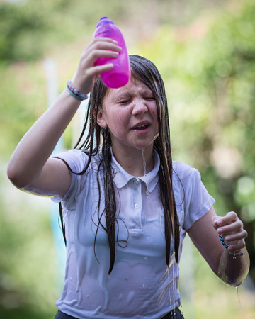 Teenage girl with long hair outside in white top empties a plastic water bottle over her hair and face.