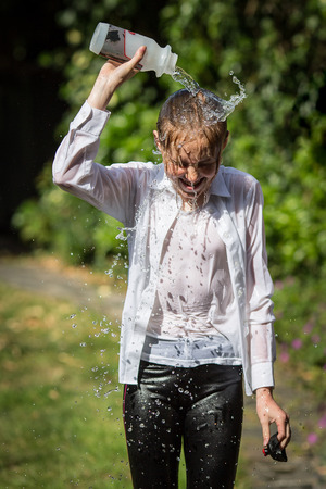 Teenage girl outside in summer in white shirt cools down by emptying a plastic water bottle over her own head.