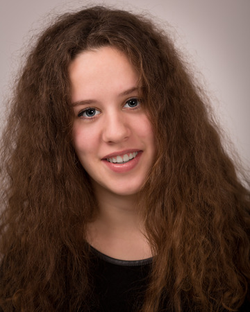 ginger hair: Studio portrait of a beautiful ginger teenage girl with long curly hair in black clothes isolated against a light grey background.