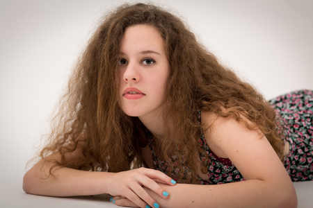 grey nails: Studio portrait of a beautiful curly teenage girl with long thick hair wearing a flower dress laying on the floor head up looking in the camera. Stock Photo