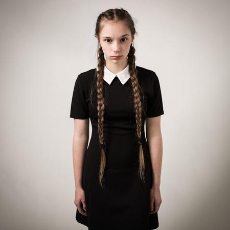 modelos negras: Estudio de retrato de una adolescente hermosa con trenzas largu�simas pelo que llevaba un vestido negro con un cuello blanco aisladas sobre un fondo gris.