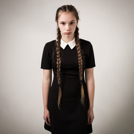 Studio portrait of a beautiful teenage girl with extremely long hair plaits wearing a black dress with a white collar isolated against a grey background. Stock Photo