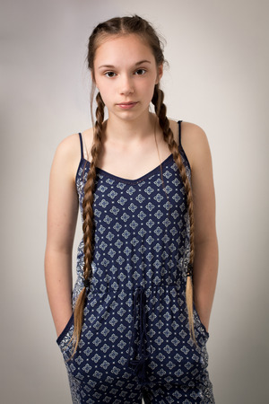 blue overall: Studio portrait of a beautiful teenage girl with extremely long hair plaits wearing a blue  overall