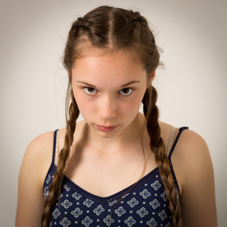 Studio portrait of a beautiful teenage girl with extremely long hair plaits wearing a blue onesie overall.