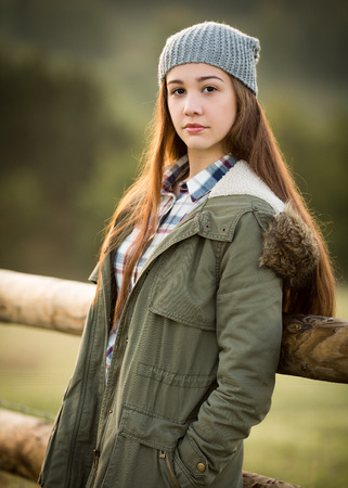 woolly: Outdoor portrait of a beautiful teenage girl with ginger long hair wearing a warm coat and a woolly hat looking. Stock Photo