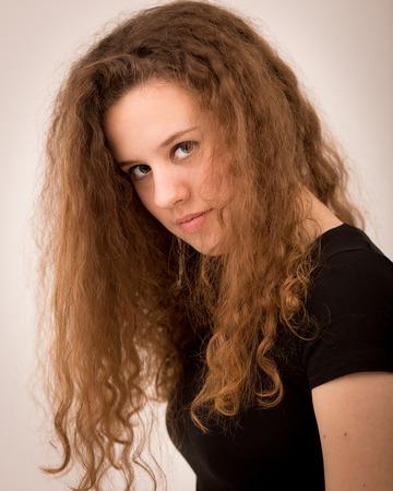 tinte cabello: Retrato del estudio de una mujer hermosa adolescente con largo y grueso pelo rizado del jengibre que mira en la c�mara contra un fondo aislado.