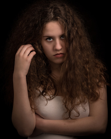 ginger hair: Studio portrait of a beautiful teenage woman with long thick curly ginger hair looking in the camera against an isolated background.