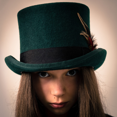 victorian girl: Studio portrait of a beautiful victorian girl with very long hair wearing a green top hat with a feather in the ribbon.