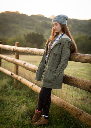 Beautiful teen girl with long hair wearing a hat, long green coat, checkered shirt, leggings and boots leaning against a fence on a farm in the hills.