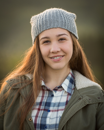 snug: Portrait of a beautiful teen girl with long hair wearing a wooly hat, checkered shirt and a green outdoor coat enjoying the sunshine.
