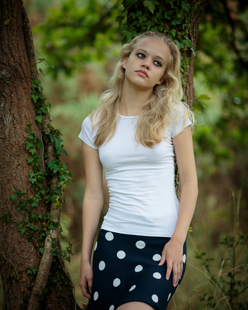 Portrait of a beautiful teenage blond girl with long hair wearing a tight white shirt and a blue skirt outside in a natural wood. Stock Photo