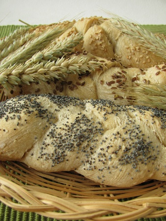 Yeast braids with poppy, sesame and linseeds in basket photo