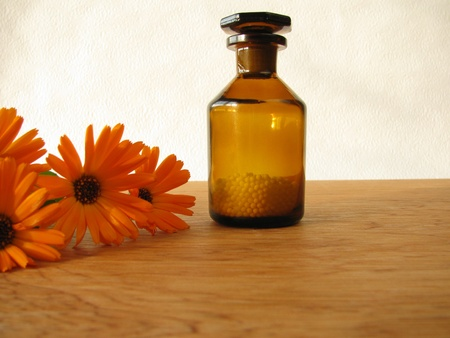 globuli: Marigold flowers and homeopathic pills in medicine bottle