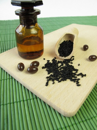 Black caraway seeds, oil and capsules Stock Photo - 13360880