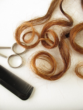 Chestnut-brown hair curls, scissors and comb photo