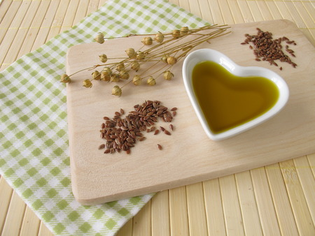 linseed oil: Linseed oil in a small heart-shaped porcelain bowl Stock Photo