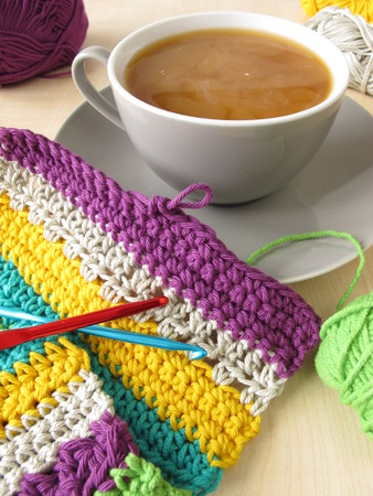 coziness: Crochet work and a cup of coffee with milk Stock Photo