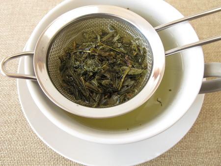 sencha tea: Green tea in tea strainer Stock Photo