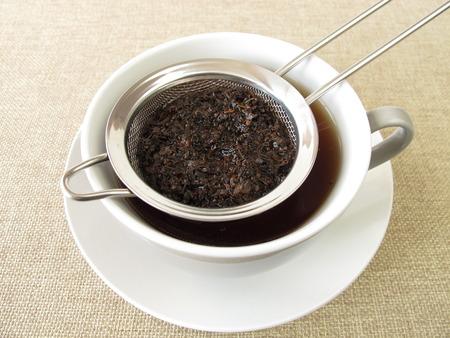 Black tea in tea strainer