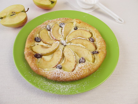 Apple pizza with raisins and powdered sugar